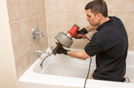 a man fixing a clogged shower drain