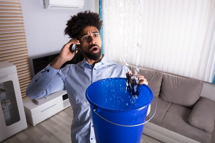 a man with a bucket collecting leaking water