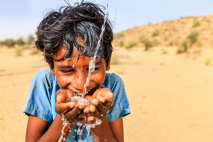 a boy drinking water from his hands