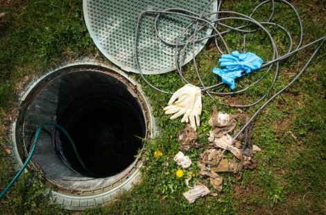 Sewer line inspection site with manhole cover open and supplies next to it on grass