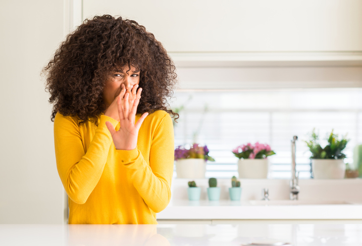 Woman standing in kitchen plugging her nose