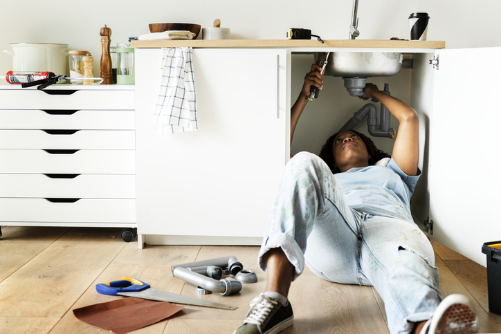 Woman laying under a sink fixing pipes