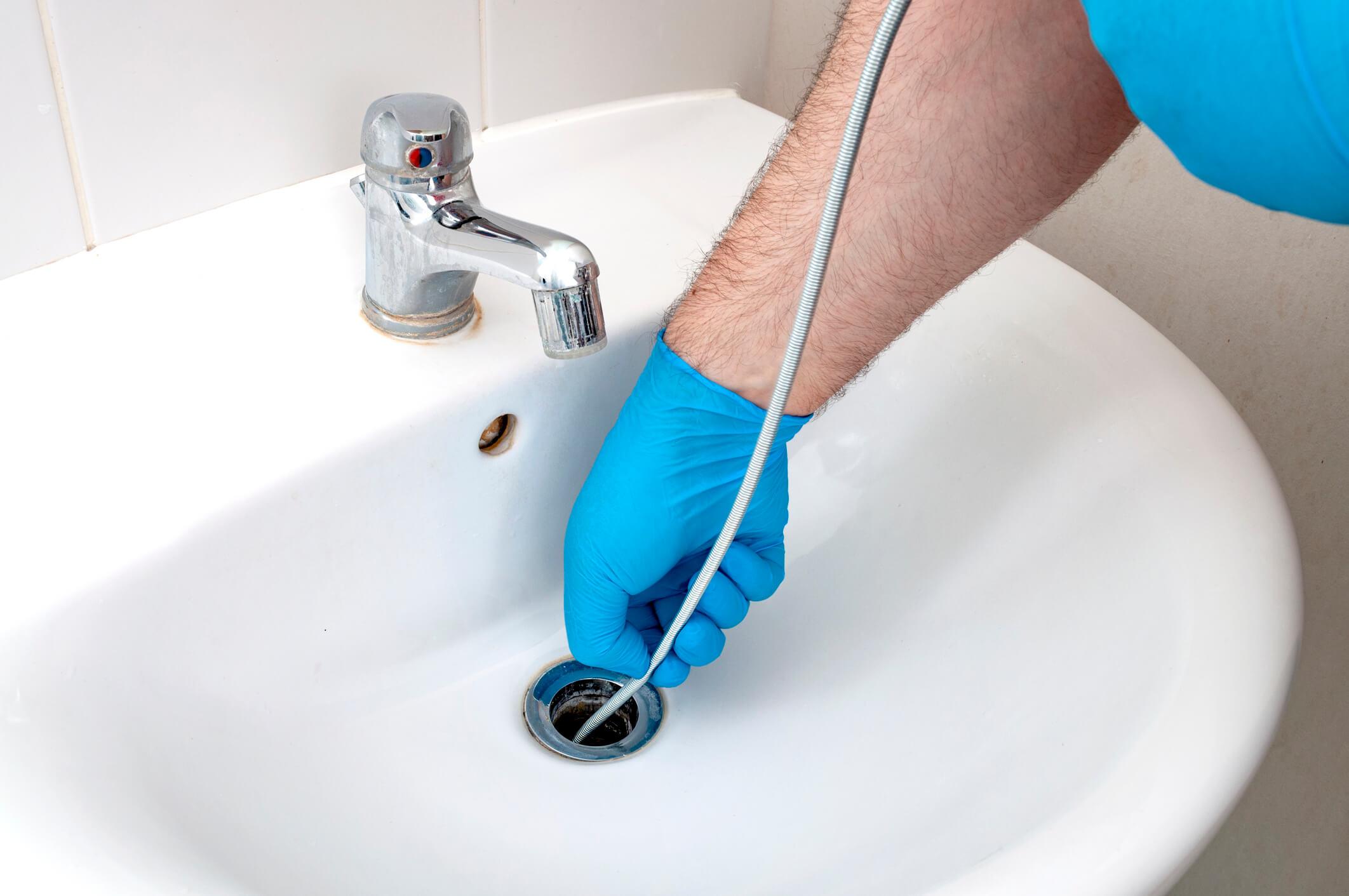 Man using a plumbing snake in sink