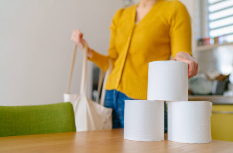 Woman picking up rolls of toilet paper