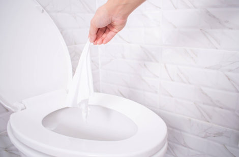person throwing a wipe into toliet