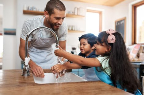 father with boy and girl at the kitchen sink smiling