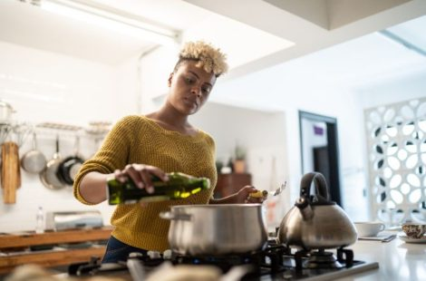 woman pouring cooking oil into pot in a modern kitchen
